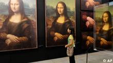 ARCHIV - Eine Besucherin betrachtet am 2. September 2009 in einer Ausstellung in Medellin, Kolumbien, Nachbildungen der Mona Lisa. Leonardo da Vincis weltberuehmtes Oelgemaelde zeigt einem Bericht der Sueddeutschen Zeitung, Donnerstagausgabe 15. Oktober 2009, zufolge nicht die Florentiner Kaufmannsgattin Lisa del Giocondo. Der Historiker Roberto Zapperi bezeichnete dies im Interview der Zeitung als ausgeschlossen. (AP Photo/Luis Benavides) ** zu APD3749 ** --A visitor looks at replicas of Leonardo da Vinci's Mona Lisa at the Da Vinci The Genius exhibition in Medellin, Colombia, Wednesday, Sept. 2, 2009. (AP Photo/Luis Benavides)