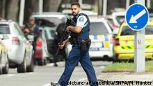 15.03.2019, Neuseeland, Christchurch: Ein bewaffneter ist in der Nähe der the Masjid-Al-Noor-Moschee im Einsatz. Nach den bewaffneten Angriffen auf Moscheen in der neuseeländischen Stadt Christchurch mit mehreren Toten hat es nach Angaben der Polizei vier Festnahmen gegeben. Foto: Martin Hunter/SNPA/dpa +++ dpa-Bildfunk +++
