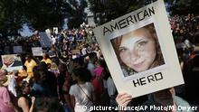 A protestor holds Heather Heyer's picture