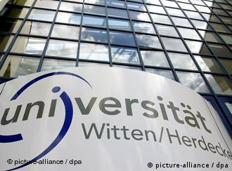 A sign outside of the University of Witten-Herdecke in front of a glass-faced university building