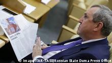 Russland Moskau - Staatsduma Mitglied Vadim Belousov liest in einer Plenarsitzung ein Magazin