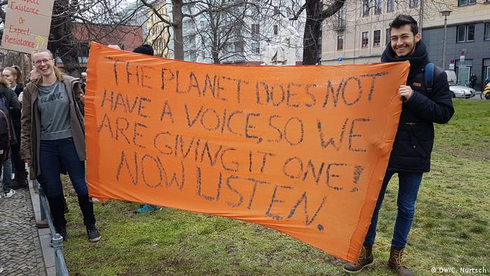 Climate protesters hold up a banner reading the planet does not have a voice, so we are going to give it one!