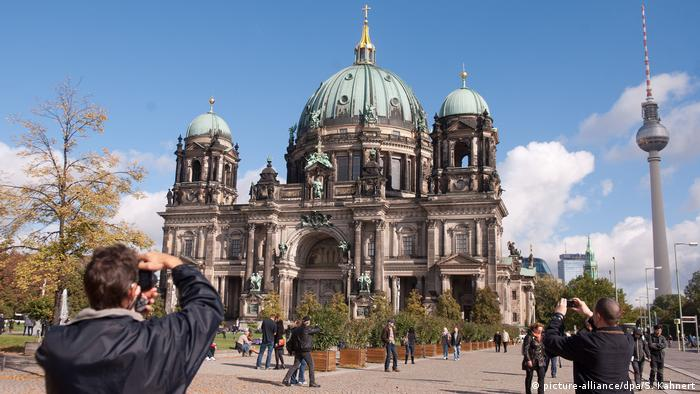 Tourists taking pictures of the Berlin Cathedral, the TV tower in the background (picture-alliance/dpa/S. Kahnert)