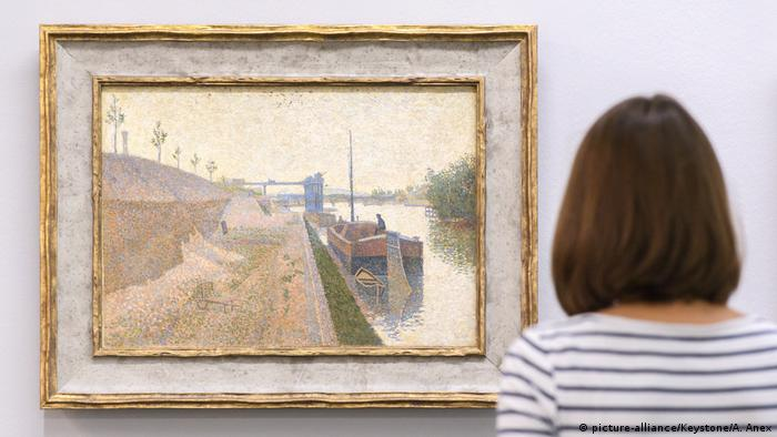 A person looks at the painting Quai de Clichy, 1887 by French painter Paul Signac