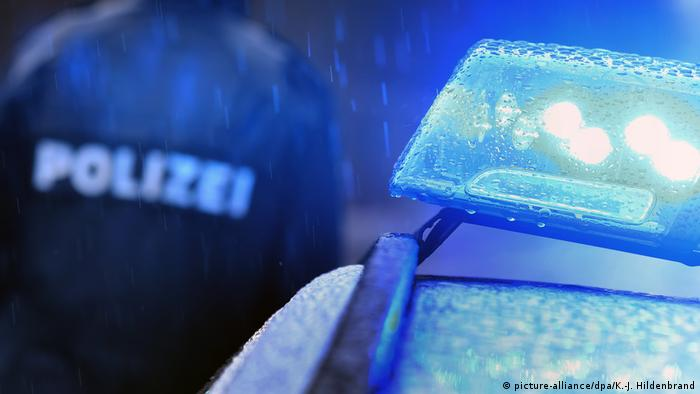 Foto mostra uma sirene azul e, ao fundo, desfocado, a imagem de um policial.