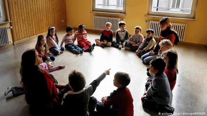 Children sit in a circle at kindergarten
