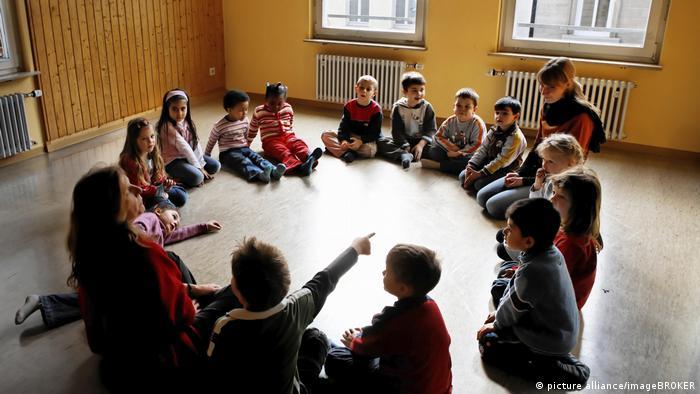 Kinder sitzen im Kreis in einer Kindertagesstaette