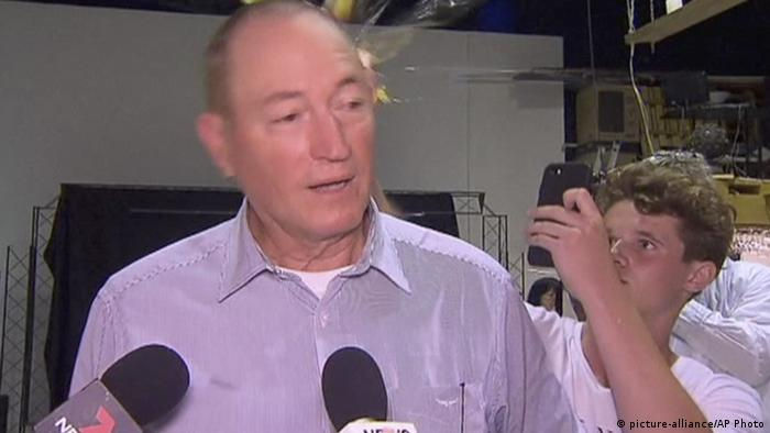 A boy films with his mobile phone as he cracks an egg against Fraser Anning's head