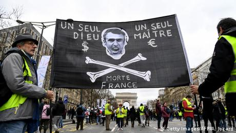 Demonstrators hold a banner depicting the French President and reading 'only one God, one Master, dead France' in Paris (Getty Images/AFP/A. Jocard)