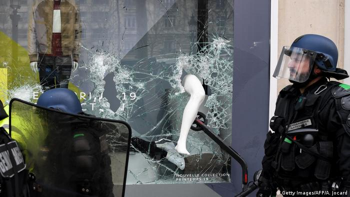 French riot police forces walk past a scooter seen in a broken store window