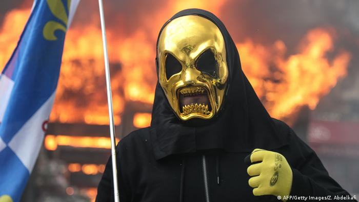 A Yellow Vest protester wearing a gold mask takes part in Paris