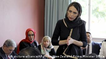 Jacinda Ardern wearing a headscarf and dressed in black holds her hands together as she speaks with a group of people (picture-alliance/AP Photo/New Zealand Prime Minister Office)