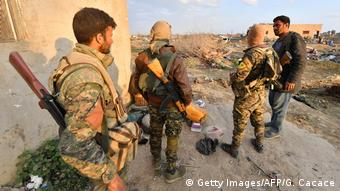 US-backed Syrian Democratic Forces (SDF) fighters stand near the village of Baghouz