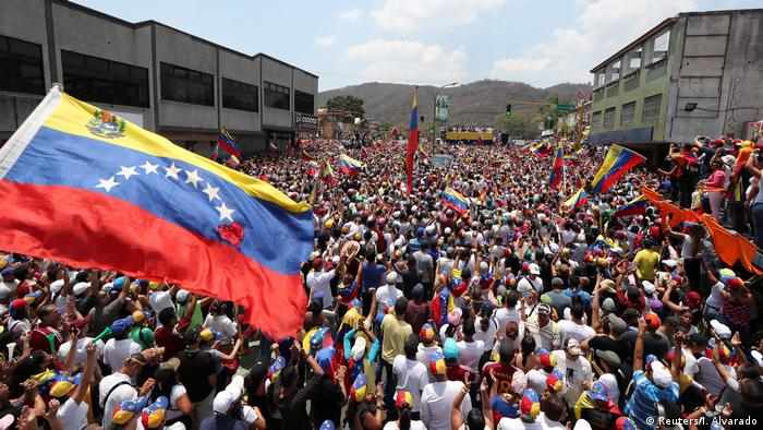 People in a crowd listen to Guaido speak as a Venezuelan flag is waved (Reuters/I. Alvarado)