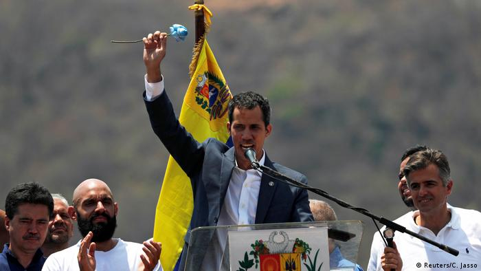 Guiado holds up a flower as he speaks into a microphone with the Venezuelan flag behind him (Reuters/C. Jasso)