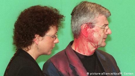 Joschka Fischer stands covered in red paint next to a woman (picture-alliance/dpa/M. Gerten)