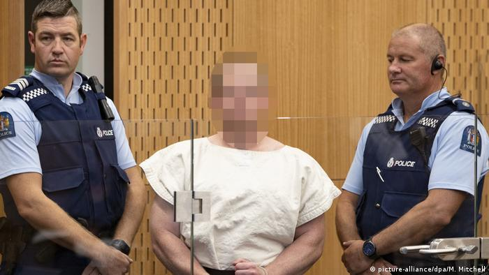 A picture of the Christchurch shooter, buarded by police. His face is pixled out to deny him publicity.