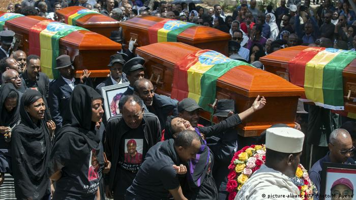 Mourners accompany empty caskets through the streets