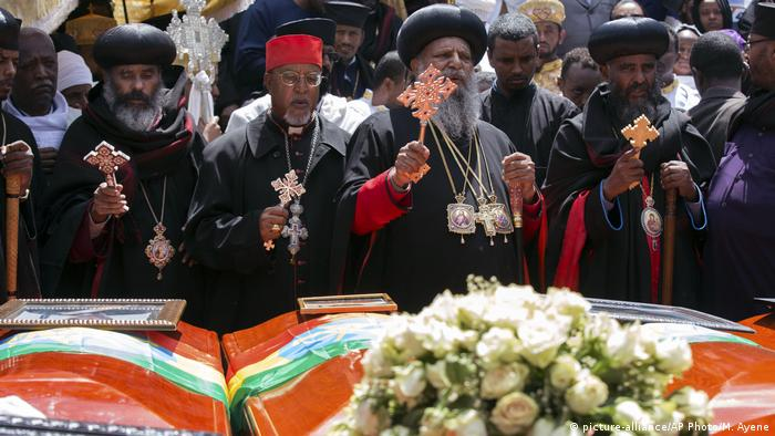 Church leaders pray next to caskets draped in the Ethiopian flags