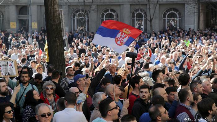 Serbian flag flies above a crowd of protesters in Belgrade (Reuters/M. Djurica)
