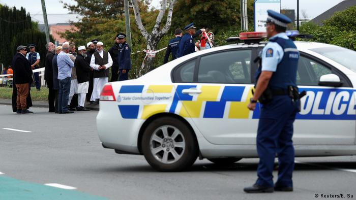 Police stand guard as members of Muslim religious groups gather for prayers at the site of the shooting outside Linwood Mosque in Christchurch, New Zealand (Reuters/E. Su)