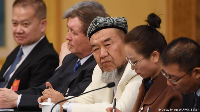 A Uighur delegate (C) attends the Xinjiang delegation meeting at the ongoing National People's Congress at the Great Hall of the People in Beijing on March 12, 2019.