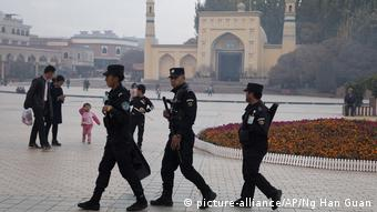 Uighur security personnel on patrol in front of the Id Kah Mosque in Kashgar, in western China's Xinjiang region