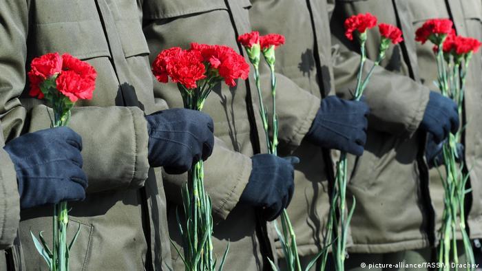 Солдаты держат в руках гвоздики