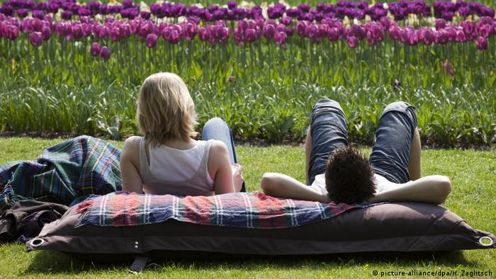 A couple sitting in the grass looking at tulips (picture-alliance/dpa/H. Zaglitsch)