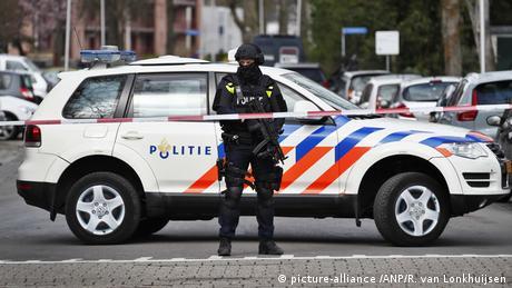 Rua interditada com uma faixa. Atrás, um policial fortemente armado em frente a uma viatura.