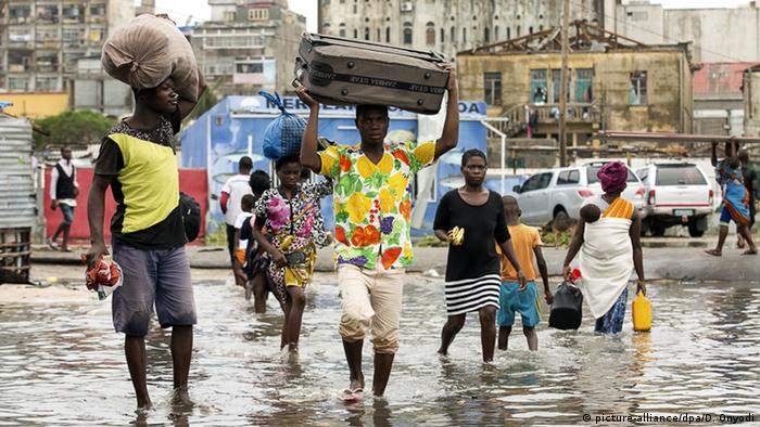 Residents of Beira walk through flooded streets with bags on their heads