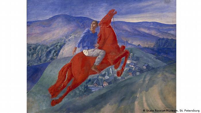 Das Gemälde Fantasie von Kusma Petrow-Wodkin: Ein Mann sitzt auf einem roten Pferd vor blauem Hintergrund. Bild aus der Ausstellung Red. Art and utopia in the land of Soviets im Grand Palais in Paris. (State Russian Museum, St. Petersburg)