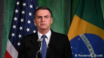 Jair Bolsonaro discursa tendo bandeiras do Brasil e dos EUA no fundo