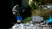 A migrant drinks as he walks with a shopping trolley across a yard of a squatted abandoned penicillin factory on November 14, 2018 in Rome's Tiburtina district, where hundreds of migrants live in precarious conditions. - Migrants addressed the media during a press conference in the building on November 14, a day after police on November 13 bulldozed a symbolic makeshift camp dubbed The Baobab in Rome which has housed tens of thousands of migrants during their journeys to northern Italy. (Photo by Filippo MONTEFORTE / AFP) (Photo credit should read FILIPPO MONTEFORTE/AFP/Getty Images)