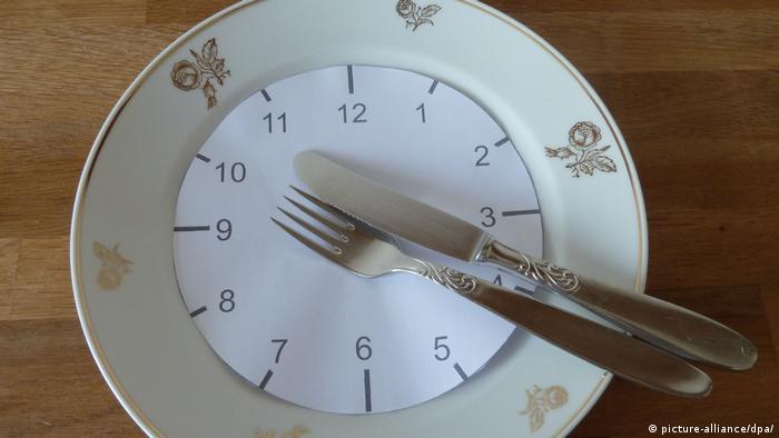Gabel und Messer liegen auf einem weißen Teller mit goldenen Verzierungen auf der sogenannten 20 nach 4 Position. Verdeutlicht mit einem Uhrzeigerblatt (Foto: picture-alliance/dpa/)
