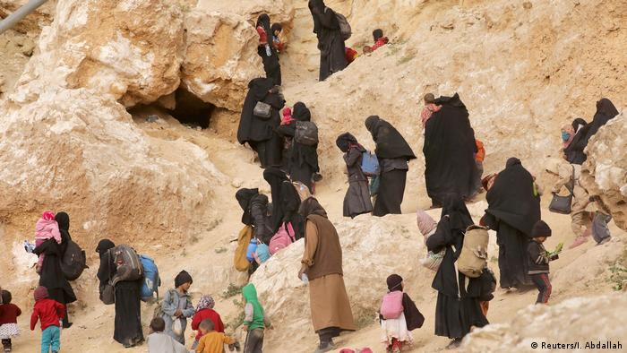 Surrendering families of IS militants walk up a rocky path