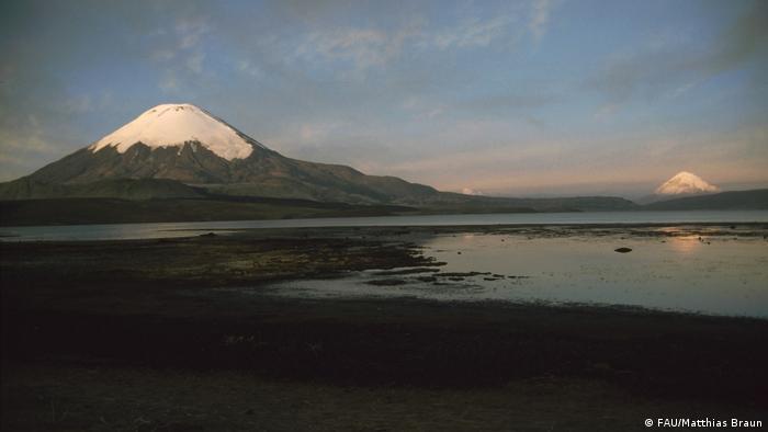 En primer plano, el volcán chileno Parinacota, de 6300 metros de altura, y más atrás, el Sajama, de 6500, en Bolivia. Glaciólogos pronostican que los hielos ubicados a grandes alturas, si bien seguirán perdiendo masa, debieran mantenerse por lo menos durante los próximos cien años.