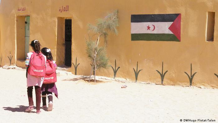 Dvije djevojčice na putu u školu pored zgrade na kojoj je nacrtana zastava Zapadne Sahare