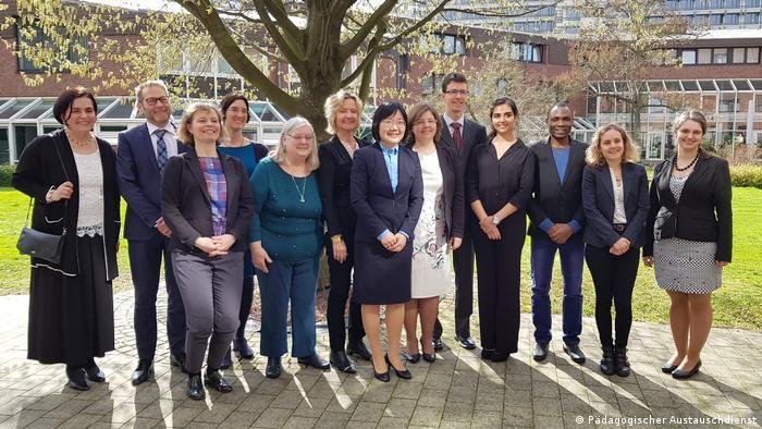 Zehn Alumni stehen im Park zusammen mit Gernot Stiwitz (PAD) und Heidrun Tempel (AA)