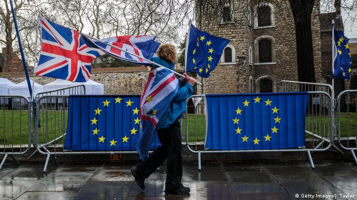 A person carrying Union Jacks and EU flags