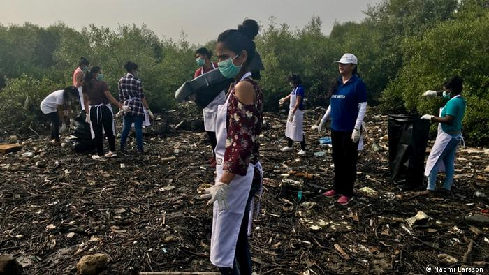 A woman stands in the foreground wearing an air pollution mask, as others behind her clean up on an empty patch of land