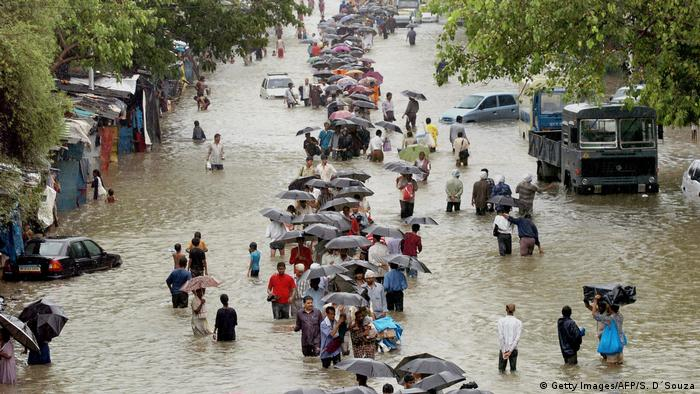 People walking down a flooded street, cars are submerged in the flood water