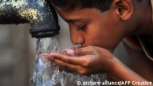 10.10.2011 Boy drinking water from a hand-pump in an impoverished neighborhood of Karachi, Pakistan