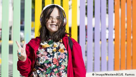 Teenager with down syndrome using smartphone, headphones, peace sign