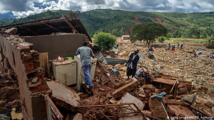 Two men look through the debris of a house in Zimbabwe which was damaged by a landslide caused by the cyclone. Rolling green hills can be seen in the distance and the sun is peeking through the clouds.