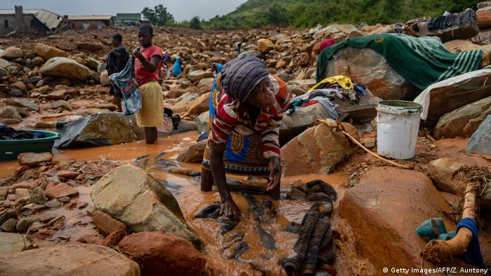 A woman in Zimbabwe washes her belongings in muddy water after Cyclone Idai passed through the community.