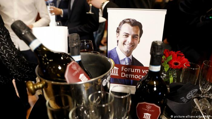 A photo of Thierry Forum, who leads the Forum for Democracy, on a table next to sparkling wine