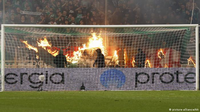 Panathinaikos fans set fire to a cloth banner during the match against Olympiacos