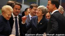 British Prime Minister Theresa May, center, speaks with Dutch Prime Minister Mark Rutte, right, and Lithuanian President Dalia Grybauskaite, left, during a round table meeting at an EU summit in Brussels, Thursday, March 21