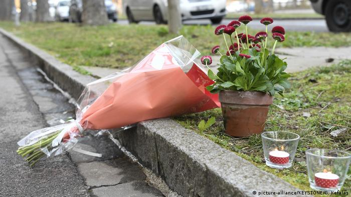 Flowers and candles lie on the footpath near where the boy was killed